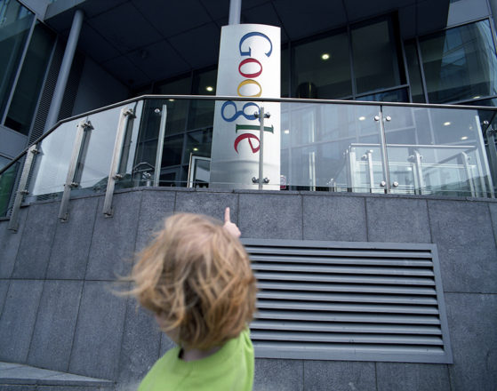 Girl points with her finger at the Google sign erected in front of the Google headquarters building