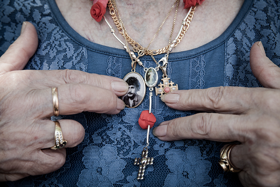 An elderly woman shows her gold jewelry on the chest