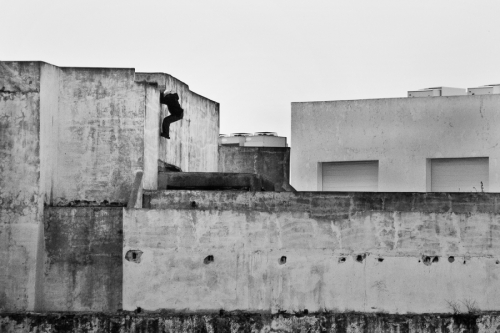 Would-be immigrant enters rooftop to get to the abandoned buildings near the port area. Tangier, Morocco