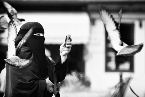 A woman in niqab takes pictures of the pigeons, Sarajevo