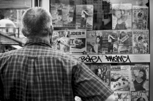 Man stands in front of newspaper shop, Sarajevo