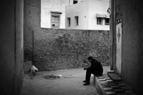 Man sits in front of the house, Kairouan