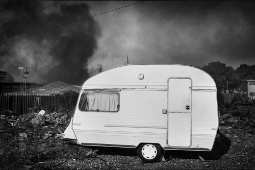 Caravan with the smoke and fire in the background