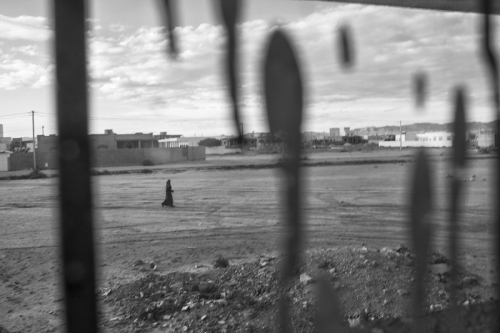 5. Women passes in the distance at the outskirts of Regueb, Tunisia