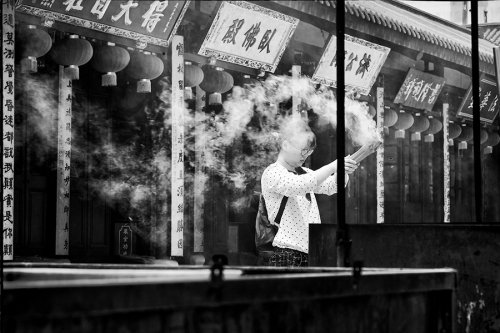 Woman holds the incense sticks in China