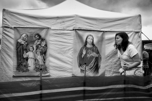 Woman passes along the images of Jesus posted on the tent