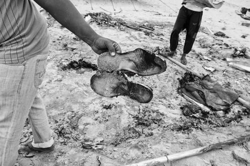 Refugee holds burned shoes, Choucha refugee camp,Tunisia