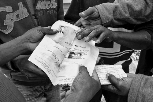 Men hold documents of a refugee who died in a fire, Choucha refugee camp,Tunisia