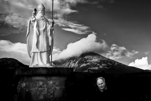Pilgrim circulates around the St. Patrick's statue with Croagh Patrick in the background