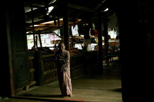 A merchant stands by her stall in a monastery. Inle Lake, Myanma