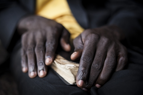 Hands held on the Bible