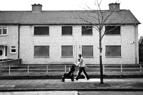 Woman walks in front of abandoned house, Dublin