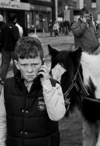 Portrait of a boy talking on the mobile phone at Smithfield horse fair, Dublin