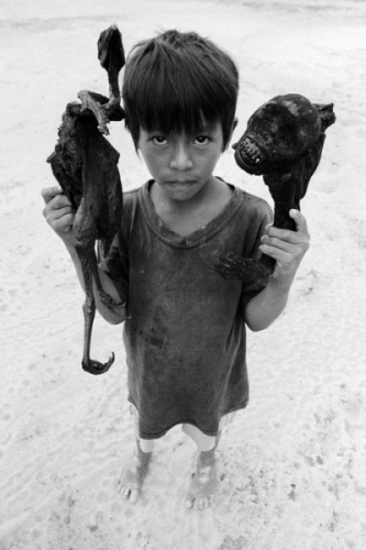 002. Matses boy holds pieces of cooked monkey